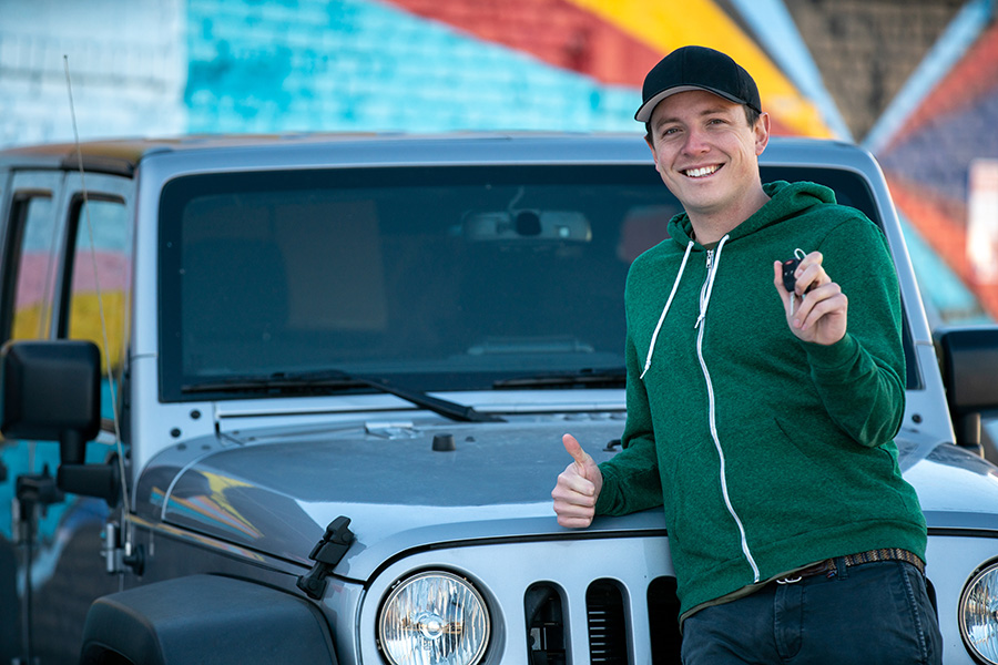 Young man in baseball hat and green hoodie stands in front of a Jeep with keys in his hand and his thumb up